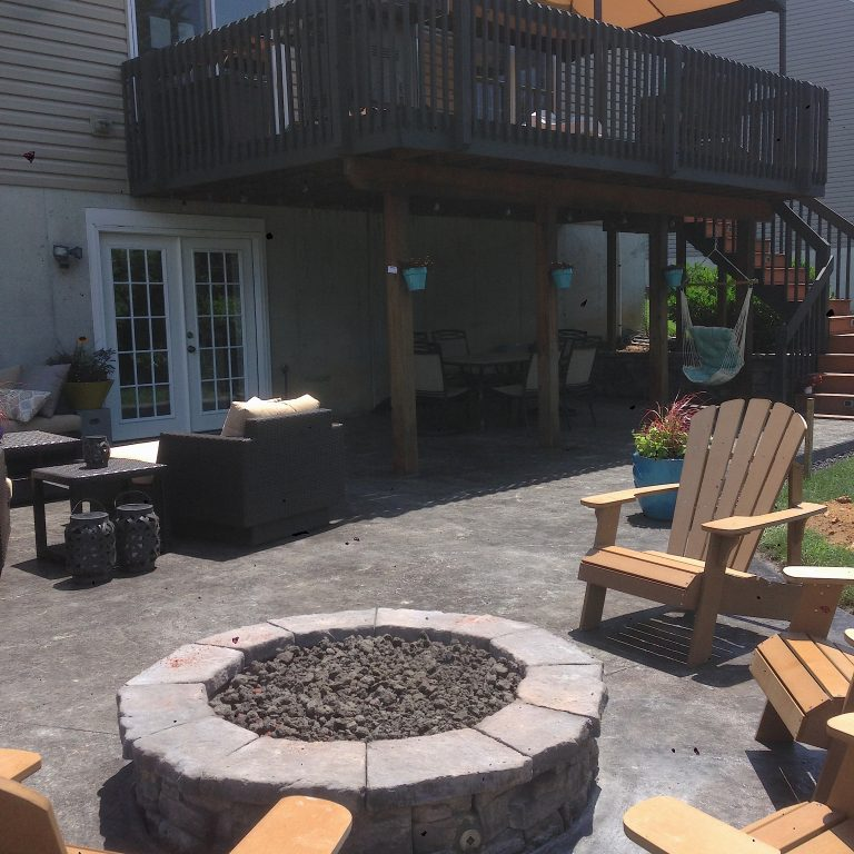 fire pit in the center of lawn chairs